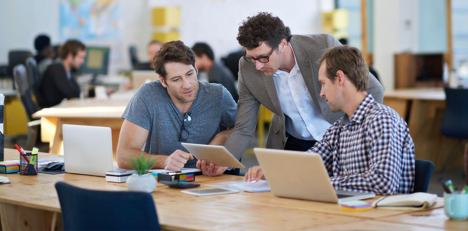 Three men looking at tablet and communicating using Business Telecommunication Systems