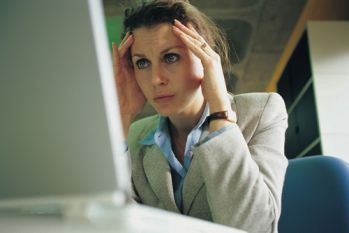 Woman holding head looking at computer